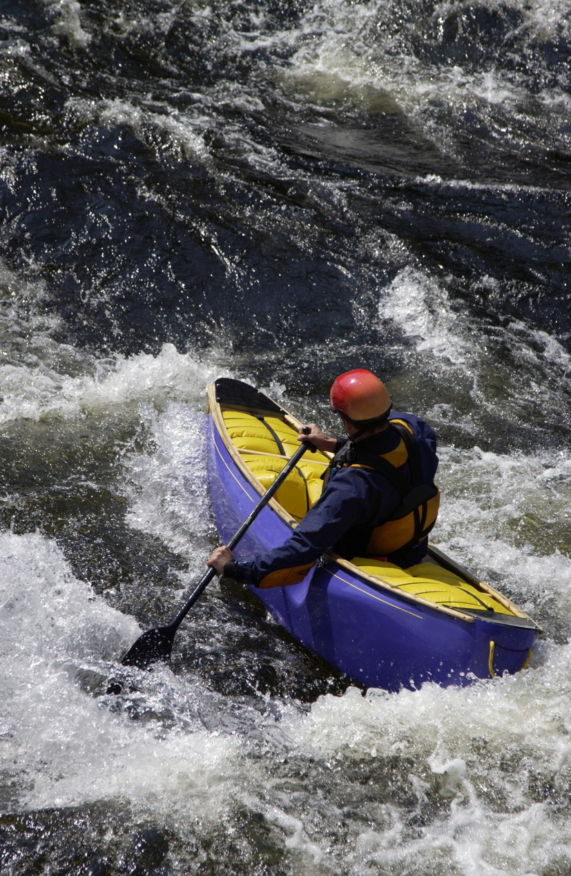 Solo Canoeist paddling in whitewater
